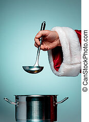 The Santa hand holding a ladle or kitchen spoon and ready...