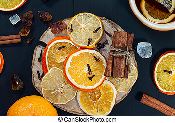 Dried slices of citrus fruits on a wooden surface black