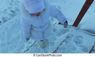 Girl child climbing stairs covered with snow. A child is...