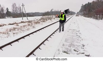 Railroad employee with snow shovel on railway