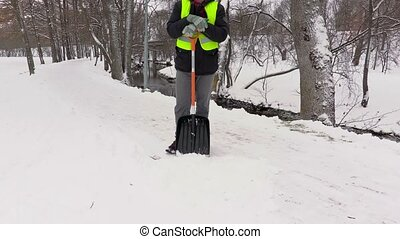 Janitor with snow shovel start cleaning path