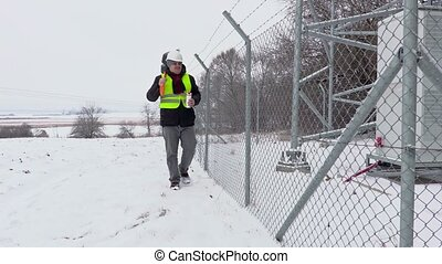 Worker with snow shovel walking near fence and start drink...