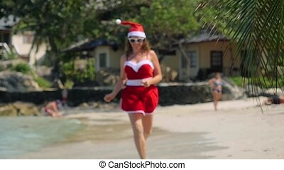 Christmas beach girl in santa hat running on the beach...