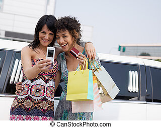 women with credit card - two women standing by limousine and...