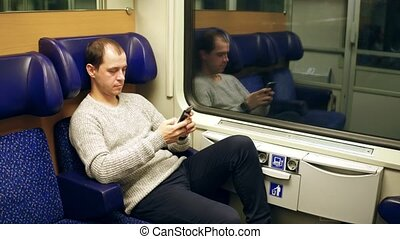 Man typing and scrolling app in his mobile phone in a train....