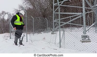 Worker with snow shovel near broken fence