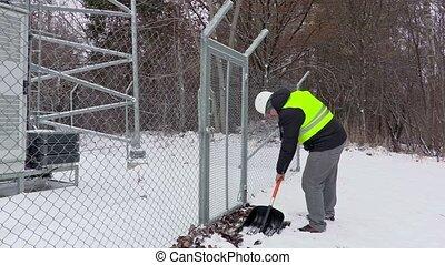 Worker clean snow near gates