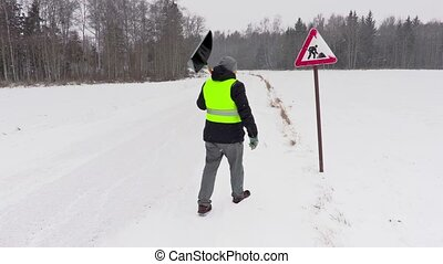 Man clean road sign from the snow
