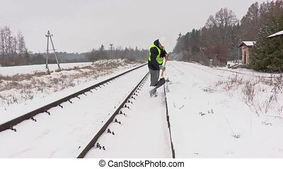 Railroad employee clean snow from the platform near railway