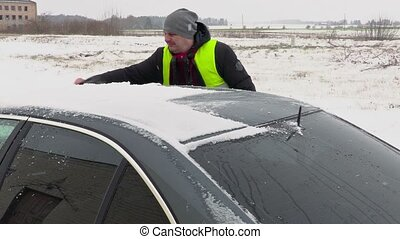Man cleaning car from the snow