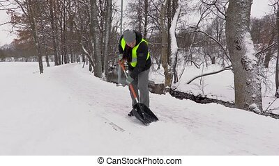 Janitor throw snow from the sidewalk
