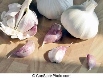 Garlic cloves - Closeup of garlic cloves on wooden chopping...