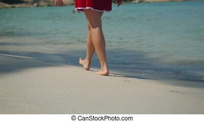 Santa Claus romantic woman walking on the beach near the sea in slow motion. Christmas and new year vacation on Koh Samui, Thailand. 1920x1080