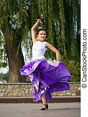 Flamenco dancer Spain woman in a long purple dress, dancing...