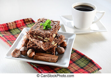 Brownie and coffee on white dish were