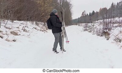 Man with pair of ski on forest road walking away