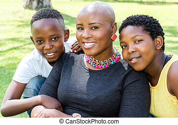 Close up of african mother with kids outdoors.