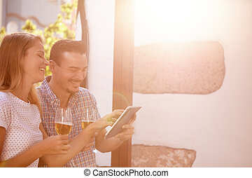 Giggling couple with touchpad and beers - Giggling millenial...