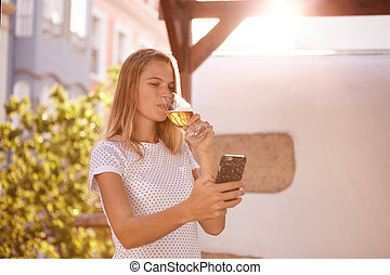 Girl looking at cellphone sipping beer - Pretty blond girl...