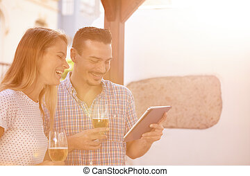 Laughing couple with beers and touchpad - Young couple...