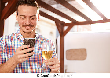 Smiling man with beer and cellphone - Handsome man looking...