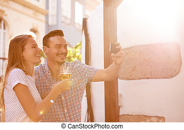 Laughing couple with beers taking selfie - Happy young...