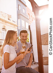 Relaxed smiling couple sitting on windowsill with beers and...