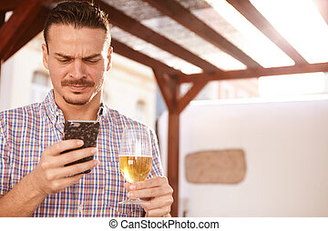 Man with a beer and cellphone - Good looking man frowning at...