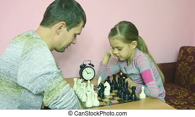 Dad and daughter in front of a game of chess greeted each...