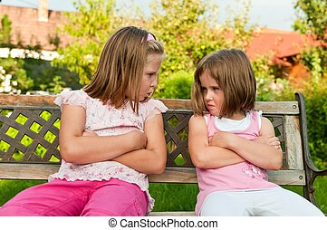Quarrel - offended sisters - Small girls (sisters) siting on...