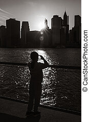 Silhouette of a boy standing on the embankment of East River...