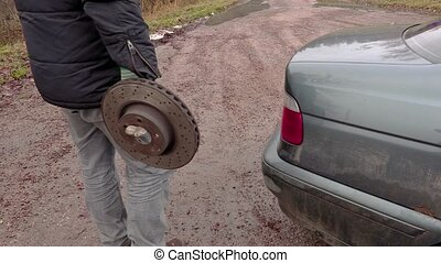 Man holding old brake disc near car