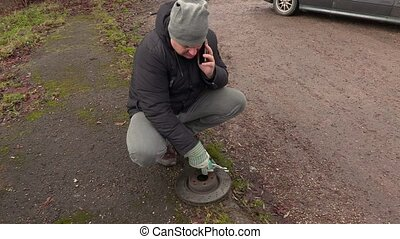 Man talking on the phone near car brake disc
