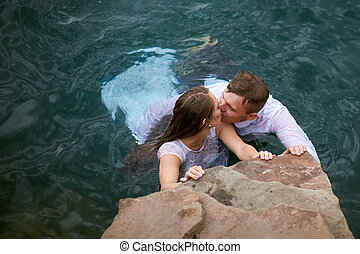 bride and groom kissing in blue water