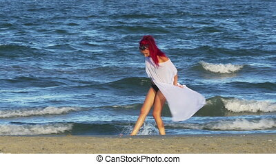 Young beautiful girl walking on the beach by the sea and...