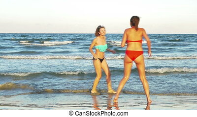 Young women playing in the ocean