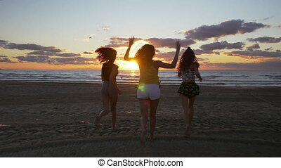 Euphoric girls running towards the sea and getting their...