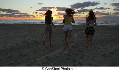 Group of teenage girls running on the beach towards the sea at sunrise