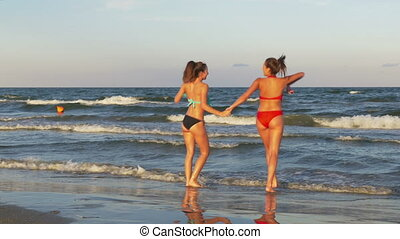 Females playing on the beach in the water and dancing