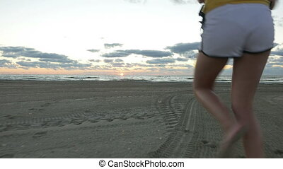 Girl running on the beach at sunrise