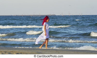 Redhead Caucasian young woman walking along the sea and...