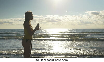 Female runner putting headphones and jogging on the shore
