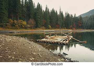 Wooden dock on the lake in the autumn forest