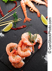 Tasty boiled shrimps with skewers on a stone plate with lime...
