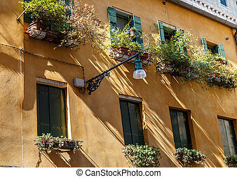 Facades Venice house with green shutters and flowers