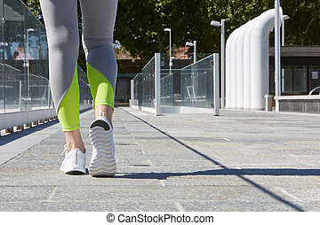 Woman with running shoes and tracksuit, outdoor in the city...