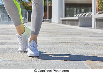 Woman with white sport shoes ready to run outdoor in the...