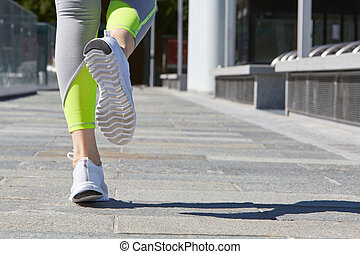 Woman running outdoor in the city in a sunny day
