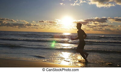 Male athlete doing workout at sunset on the beach in slow...