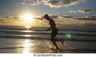 Male running on wet sandy beach during workout in slow...